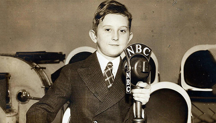 A child dresses up as a 1940s style announcer