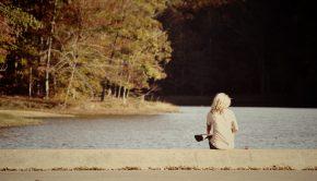 Woman sitting alone on a dock by a lake.