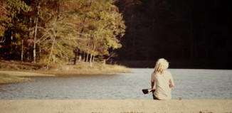 Woman sitting alone on a dock by a lake.