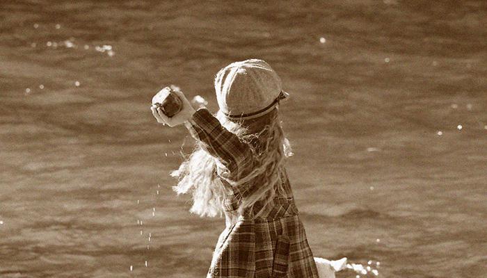 A girl throws a rock into a pond