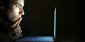 Man looks at laptop
