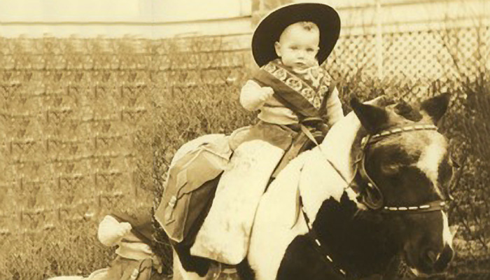 A baby sits on a horse, dressed as a cowboy
