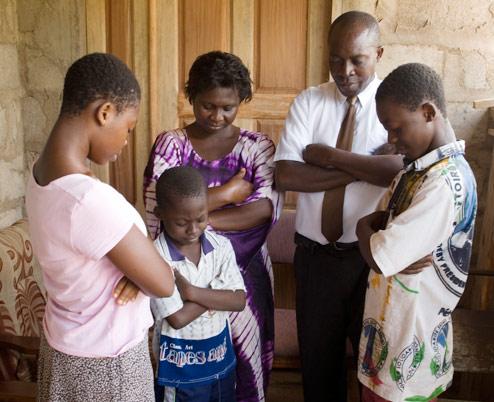 Family kneeling in prayer to dedicate their home