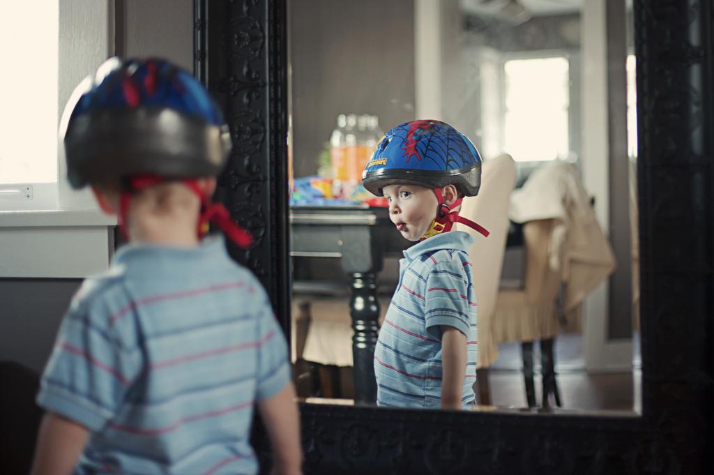 Kid in bicycle helmet poses in mirror
