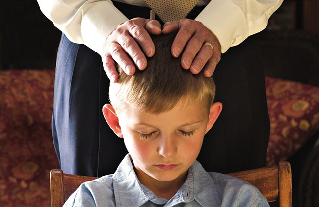A Father gives a priesthood blessing to his son