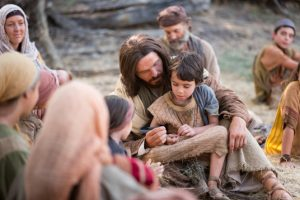 Jesus sitting on the ground with a child