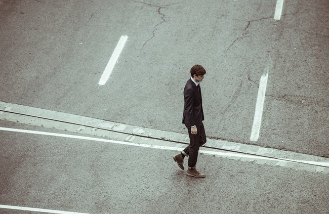 Sad man in a suit walking on sidewalk