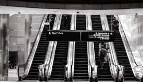 a set of escalators in an airport photographed in black and white