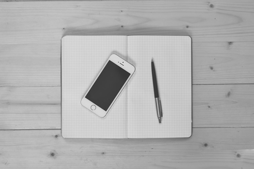 Black and White photograph of a notebook, phone, and pen on a table