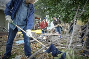 Men cleaning up fallen trees during service project