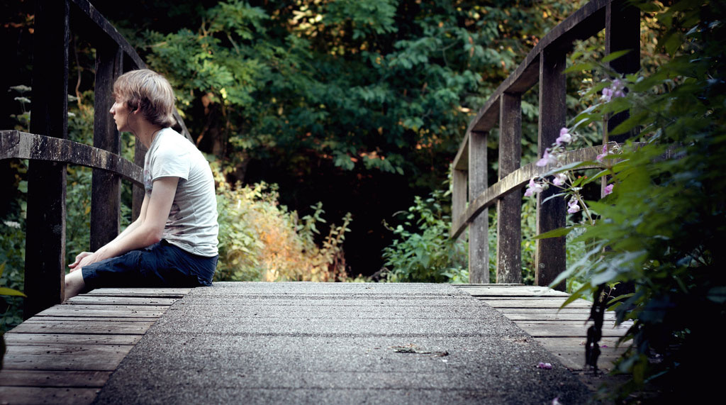 Teen Boy Listens to Music on a Bridge
