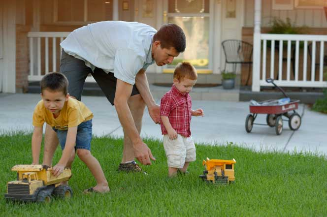 A dad playing trucks with sons