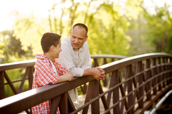 Father and son talk on bridge