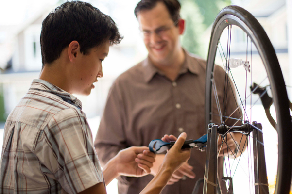 Dad helps son repair bicycle