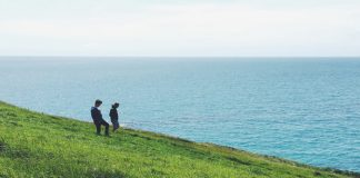 Two teenagers walking on a grassy hill by the sea