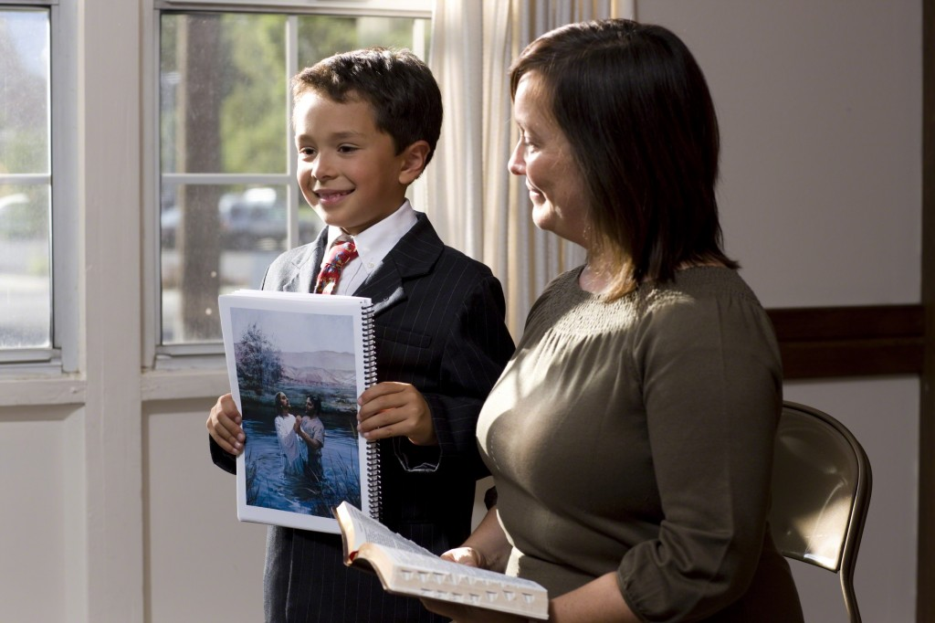 Woman teaching with little boy holding a picture of Christ