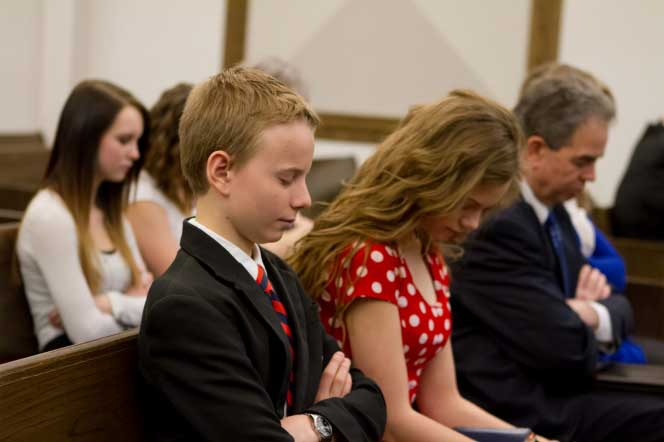 A family worshiping during sacrament meeting