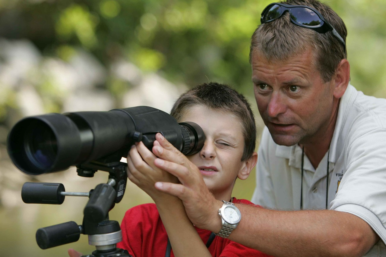 Father and son looking through telescope.
