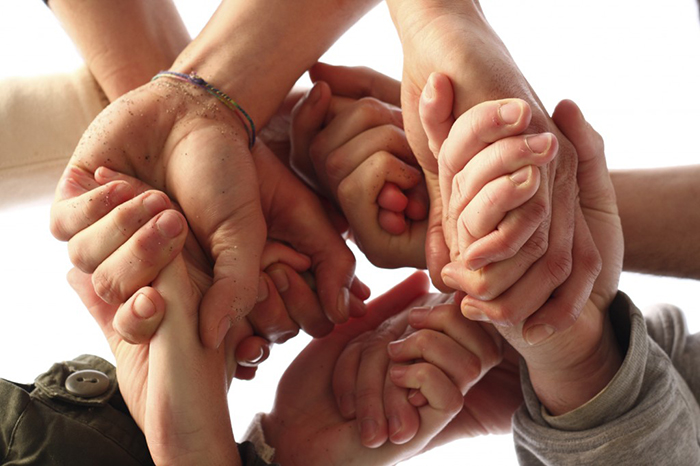 Various hands give each other support