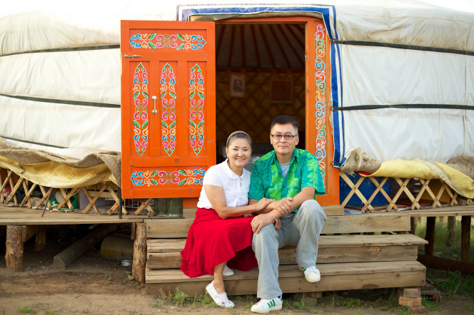Mongolian couple sitting in front of their yurt