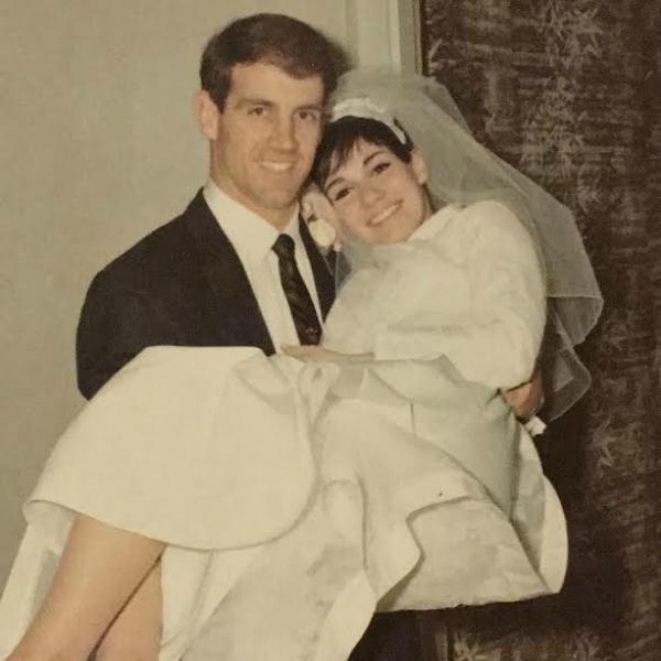 A happy groom carrying his bride