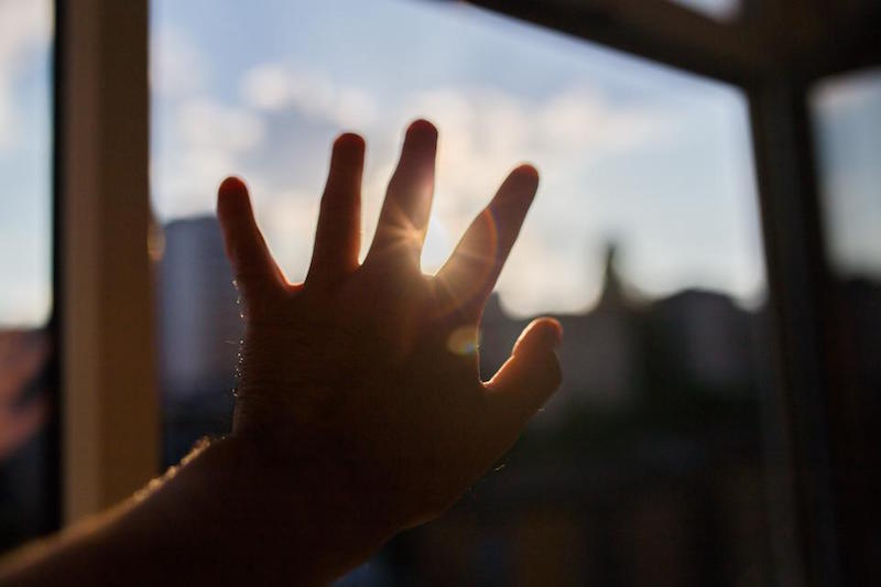 a hand reaching for the sun in hope
