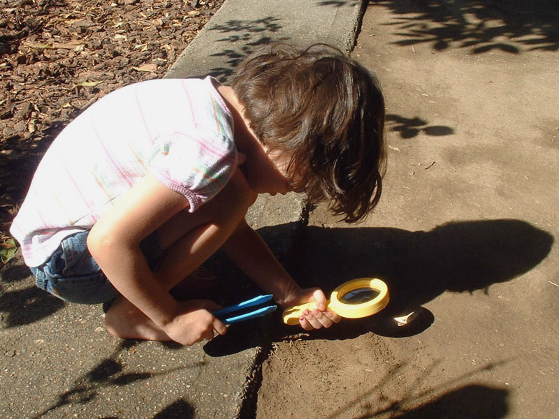 girl using magnifying glass compares to how to magnify your calling