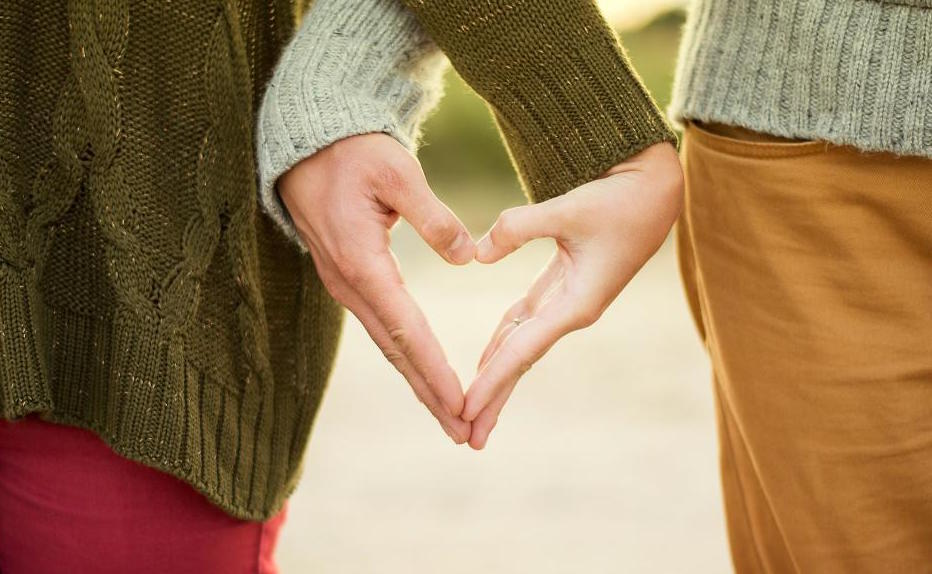 couple's hands shape a heart