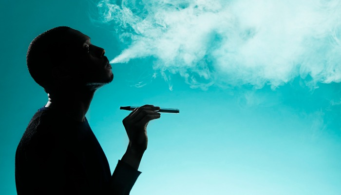 man on blue background smoke e-cigarette