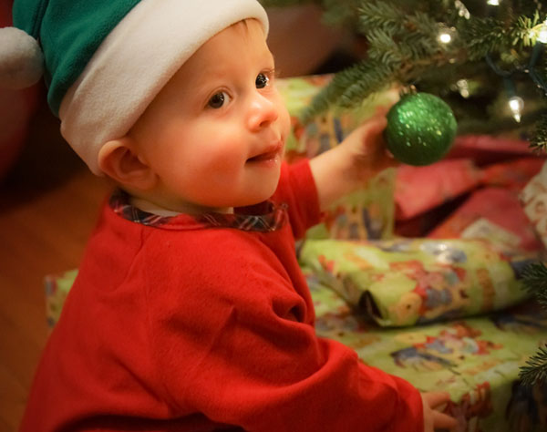 Child waits by presents in Santa Hat