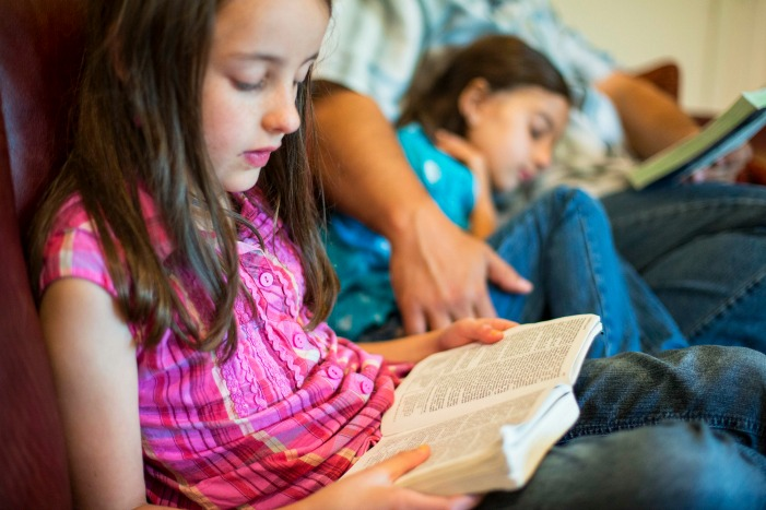 girl reads scriptures with family