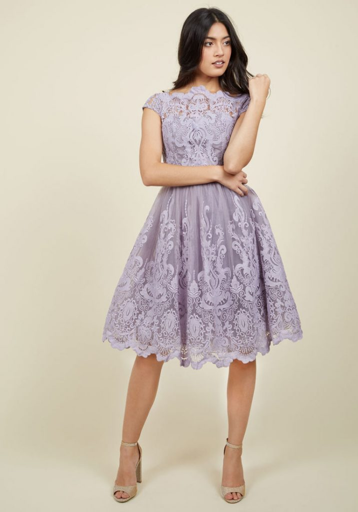 A woman in a lilac lace knee-length prom dress.