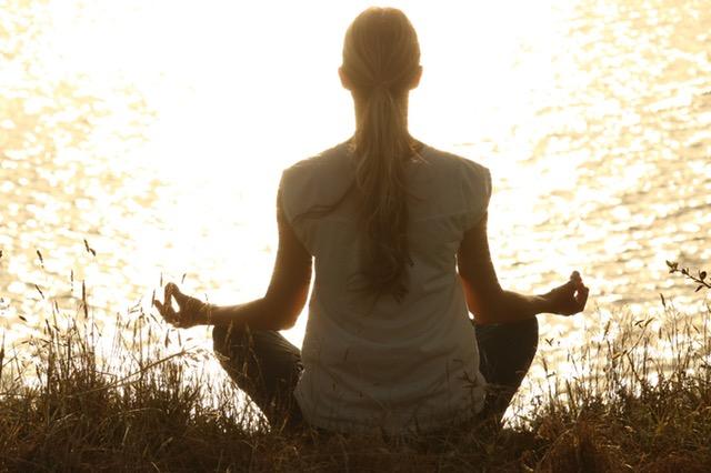Woman Practicing Meditation on riverbank