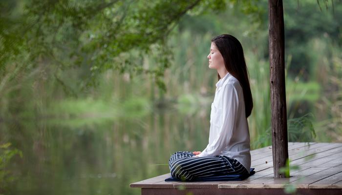 Woman meditates on dock