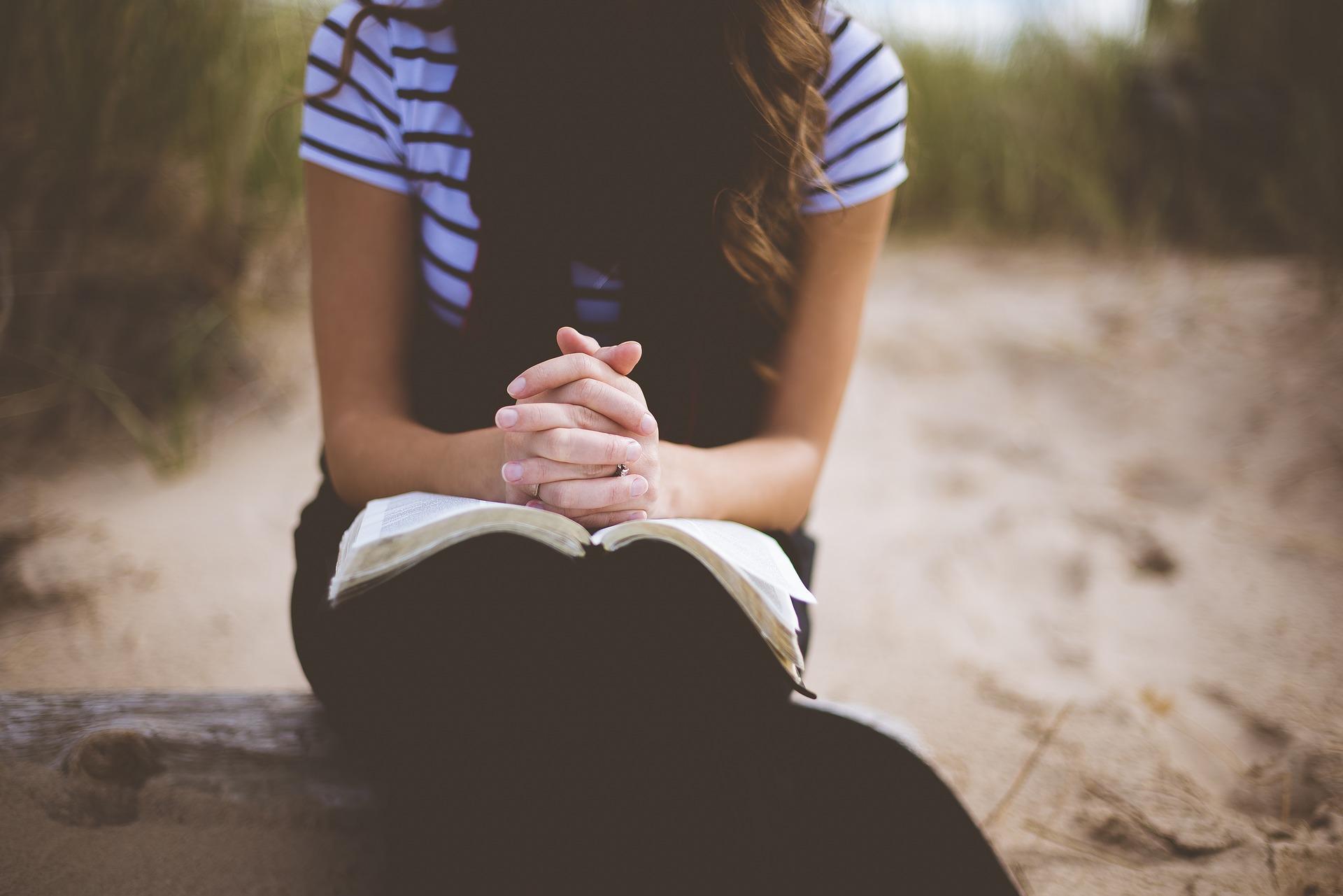 Woman praying on beach