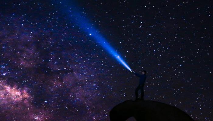 Man with flashlight looking at stars