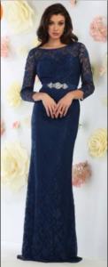 A woman wears a floor-length navy prom dress.