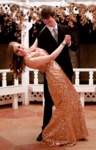 A boy dips a girl in a glittery prom dress.
