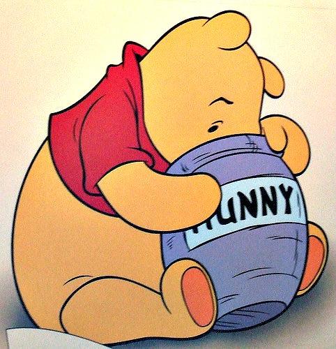 Winnie the Pooh with his face in a pot of Hunny