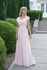 A woman wears a floor-length pink prom dress.