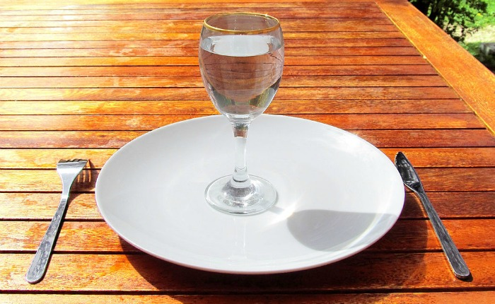 Glass of water on empty plate with fork and knife on table