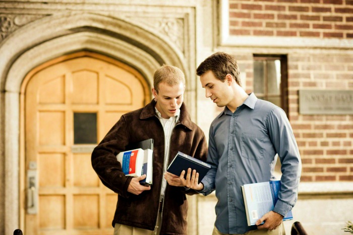 A college student shows his friend a Book of Mormon.
