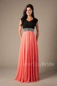 A woman wears a pink and black prom dress.