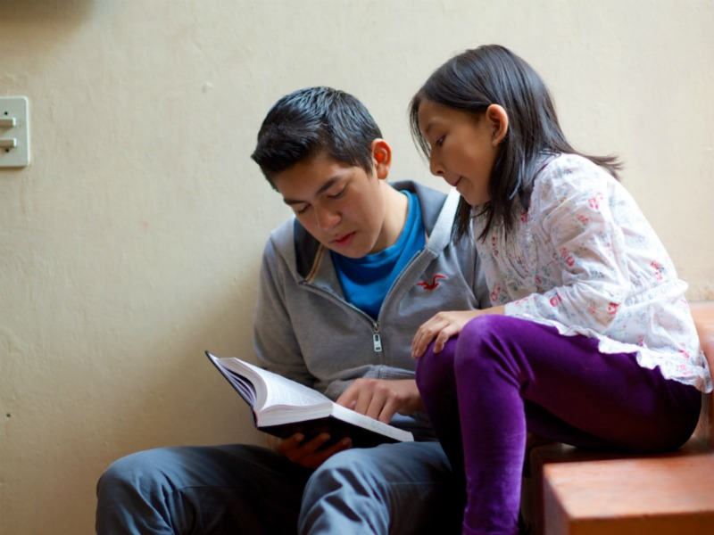 A brother and sister read the scriptures on some stairs.