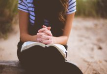 girl praying with scriptures in her lap