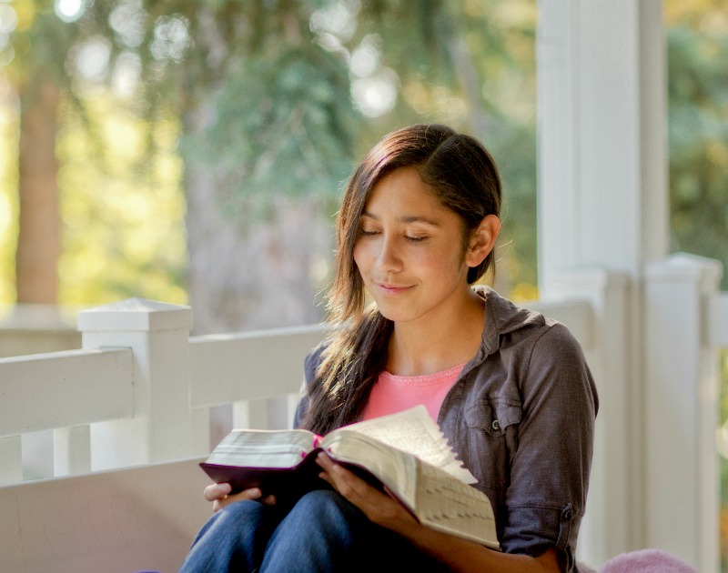 A girl in a pink shirt reads the scriptures on a porch.