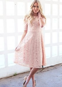 A woman models a pink lace prom dress.