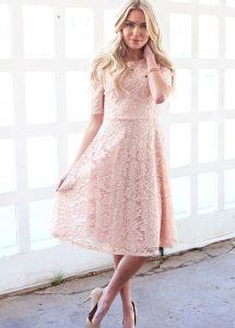 A woman models a pink lace prom dress.