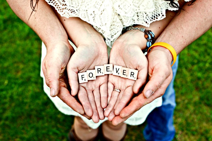 Couple Holding Hands and holding letters that spell forever