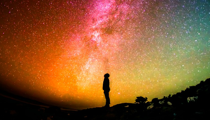 Silhouette of man looking at the Milky Way galaxy at night